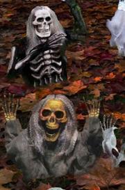la foto rappresenta alcune decorazioni halloween con zombie e scheletri che escono dal terreno